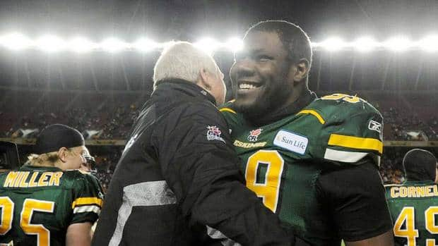 Edmonton Eskimos' Jermaine Reid, 99, gets a hug from defensive coach Kit Lathrop after beating the Calgary Stampeders in the 2011 West semi-final. Reid was traded to the Grey Cup champion Argonauts on Friday.