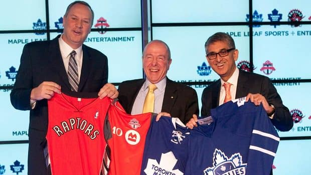 Bell Canada president and CEO George Cope, left, MLSE chairman Larry Tanenbaum, centre, and Rogers Communications president and CEO Nadir Mohamed pose with team jerseys at a press conference in Toronto last December.