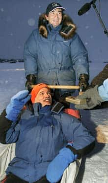 NDP Leader Jack Layton takes a dogsled ride with sled owner Grant Beck in Yellowknife, Wednesday, Dec. 23. (CP Photo/Chuck Stoody)