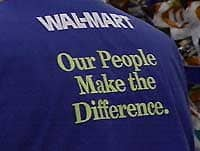 """Image of a Wal-mart worker wearing a uniform that reads: """"Wal-mart: Our people make the difference."""""""
