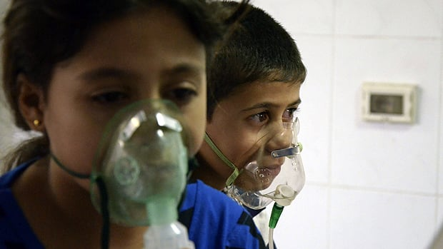 Two unhappy Syrian children with oxygen masks on