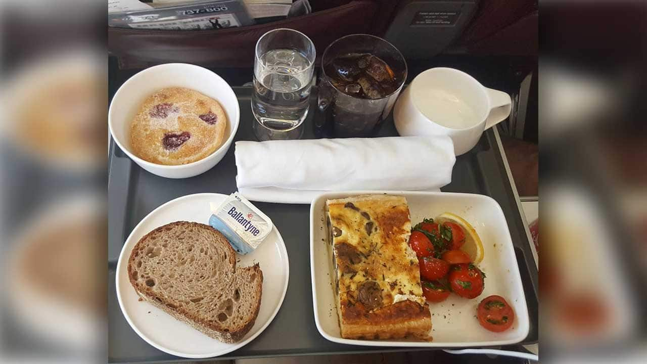 Airline meal of goat cheese pie, a bread roll and a side salad, served with a stuffed pastry for dessert.