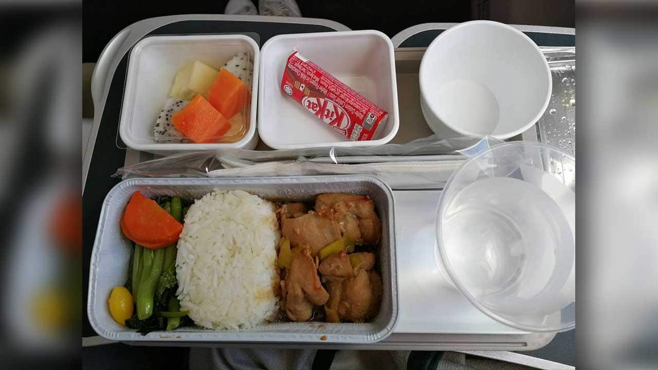 Airline meal of grilled chicken, rice, roasted veggies with a side of exotic fruit and a mini KitKat bar. Served on an airline tray with a cup of water.