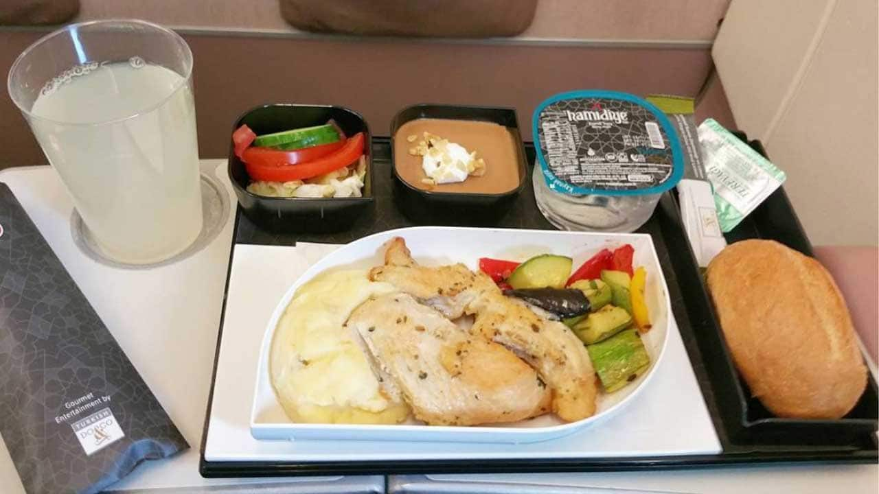 Airline meal of chicken, grilled vegetables and mashed potatoes with gravy. Served with a side salad, bread roll and chocolate mousse dessert, topped with whipped cream.