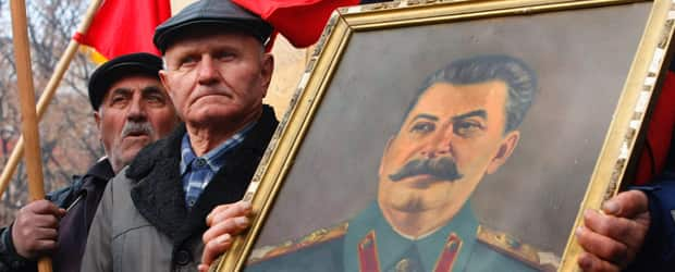 A Georgian holds a portrait of Soviet dictator Joseph Stalin during a rally marking Stalin's 132nd birthday anniversary in his home town of Gori, 80 kms (50 miles) west of capital Tbilisi, Georgia, Dec. 21, 2011. (AP Photo/Shakh Aivazov)