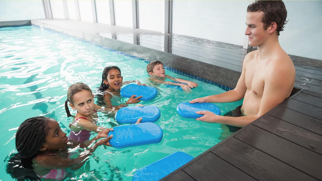 kids in swimming class at public pool with instructor
