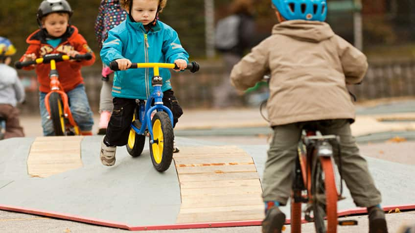 Kids learning to ride on balance bikes in a bicycle playground in Denmark.
