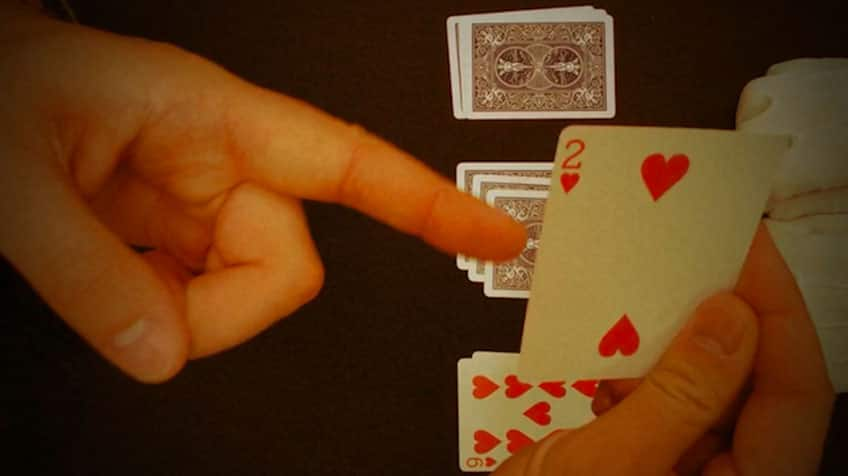 Hand points out at two of hearts.