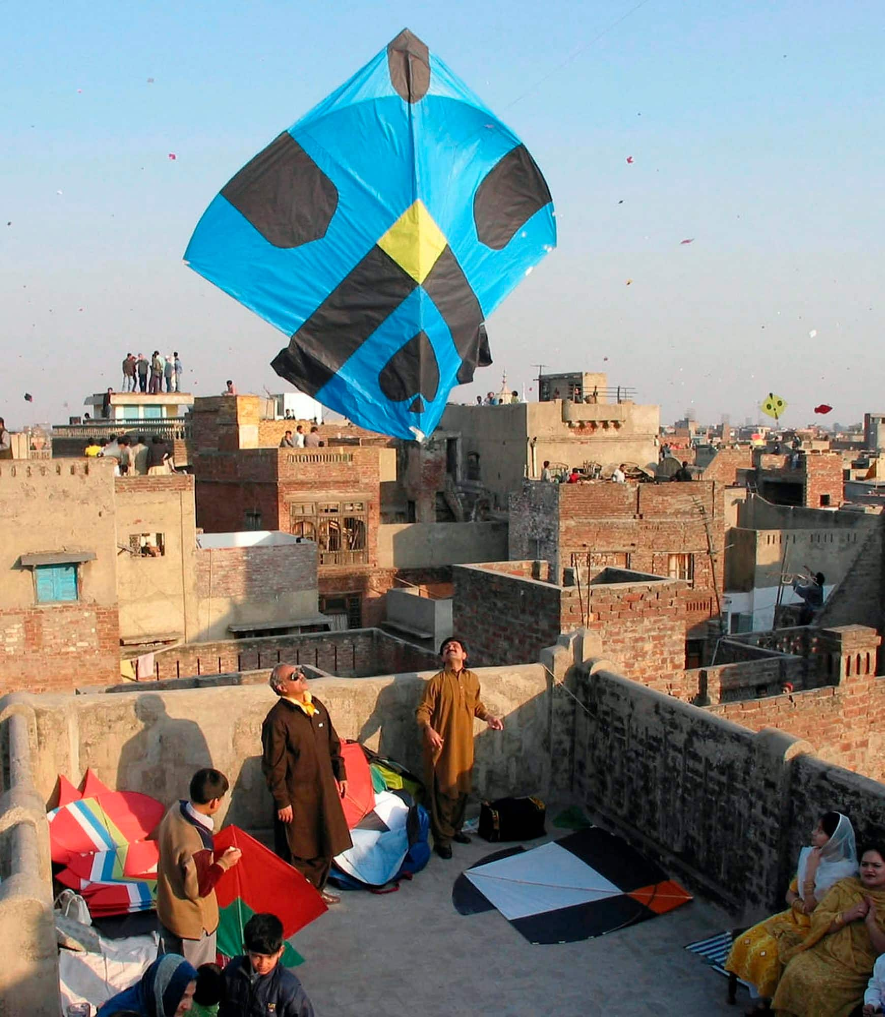 A family flies a blue and black kite on a rooftop in Lahore, Pakistan.