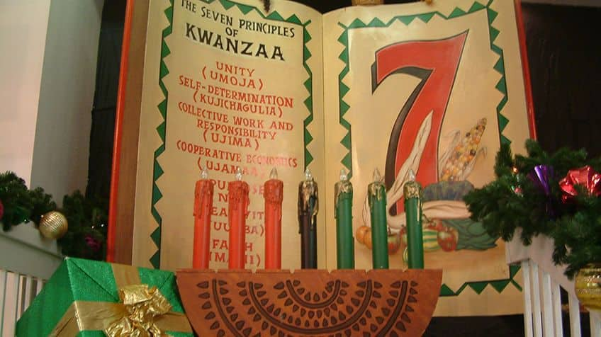 Kwanzaa candle holder (called kinara) on altar with a large book with the seven principles of Kwanzaa.