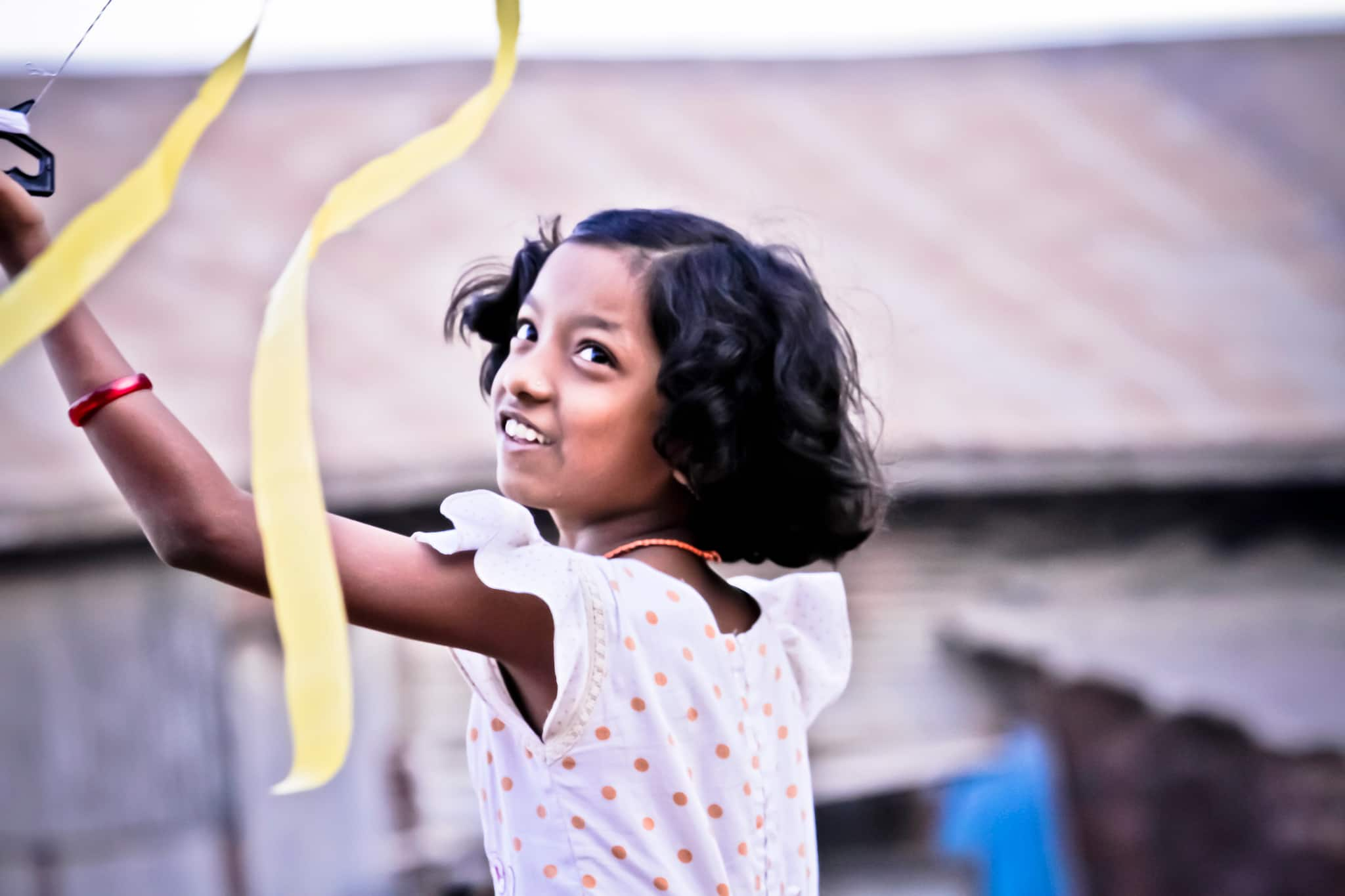 Girl looking up at her kite with yellow tails.