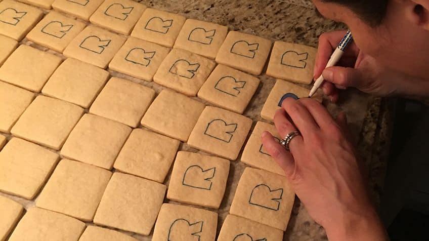 Baker is decorating cookies.