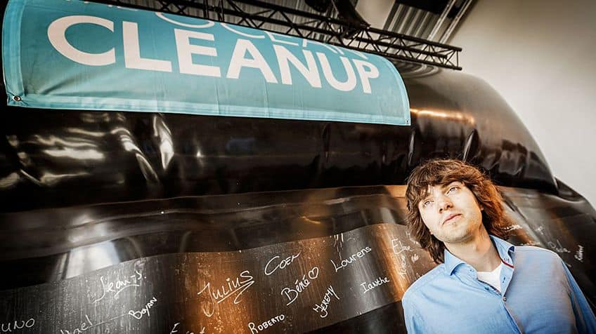 Boyan Slat stands in front of the Ocean Cleanup sign.