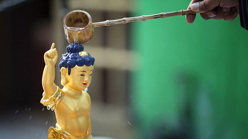 Buddha statue gets a ladle of water poured on him.