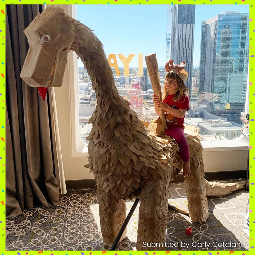 Little girl in a hotel room by a window riding a big dinosaur made of recycled materials