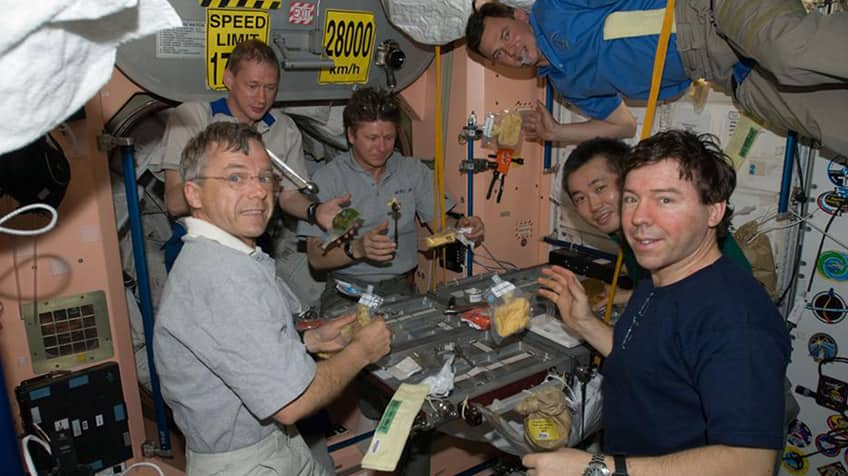 Astronauts eat together in the International Space Station.