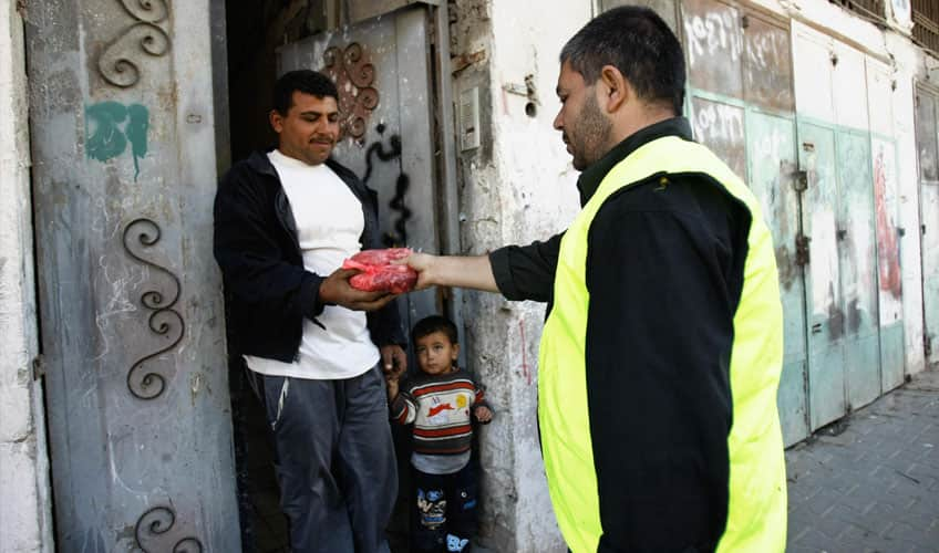 A man handing meat to a less fortunate family