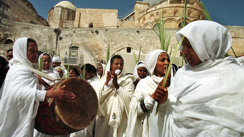 Ethiopian women dressed in white hold palm fronds outside a church.