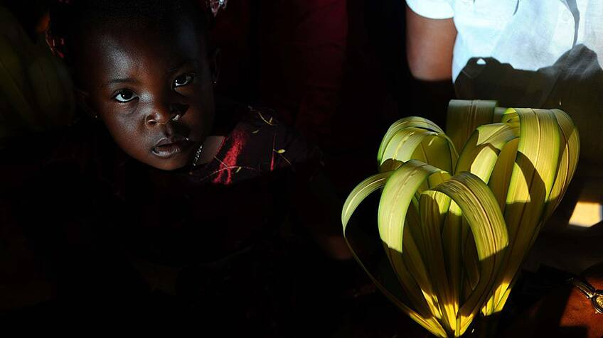 A young Haitian girl looks up at the camera.