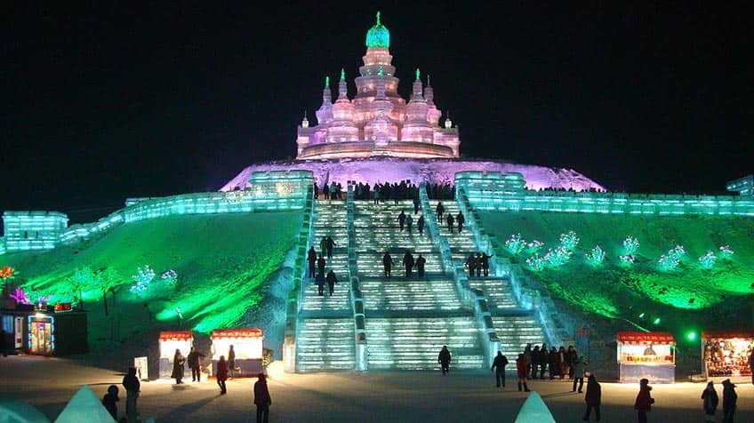 Ice staircase leading up to a lit up ice castle.