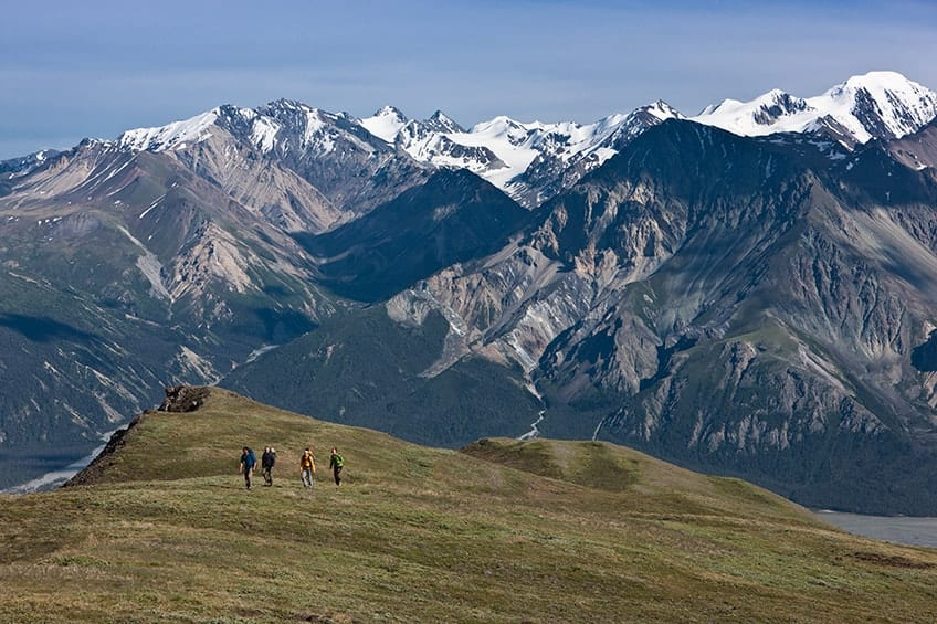 people hiking on the green mountainside during the summer months
