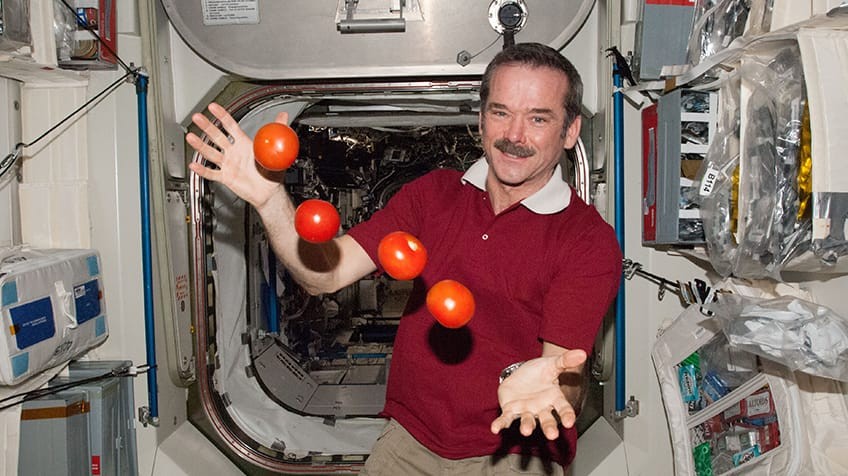 Commander Chris Hadfield shows off floating tomatoes.