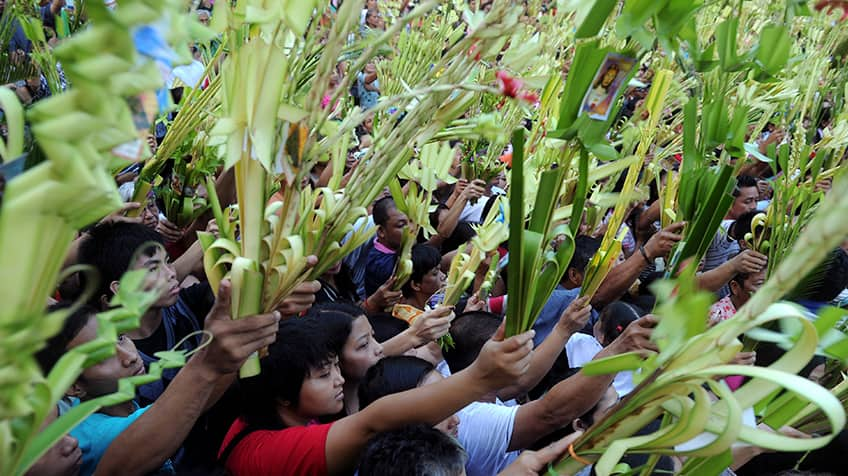 People hold palaspas, which are woven palm fronds.