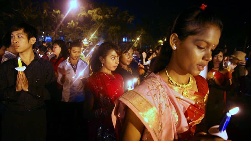 Indonesian Buddhists pray with candles on the street.