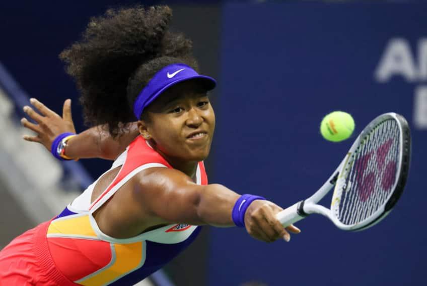 Naomi Osaka makes a funny face as she hits the tennis ball