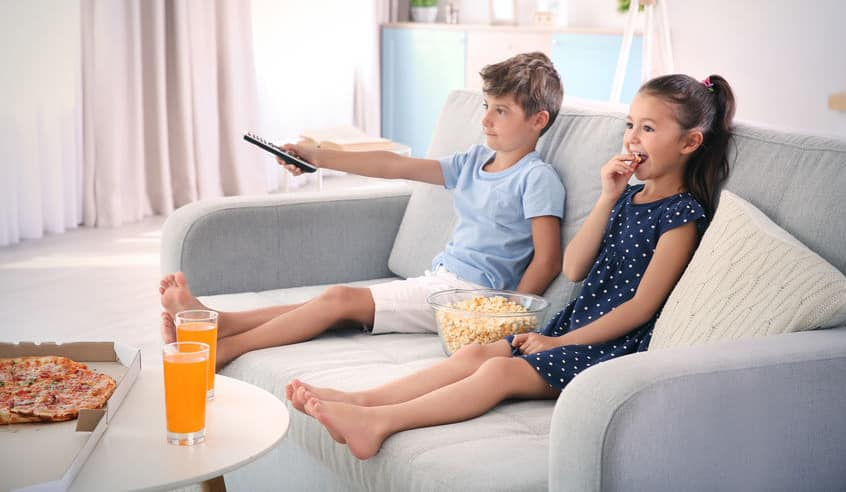kids sitting on a couch using a remote
