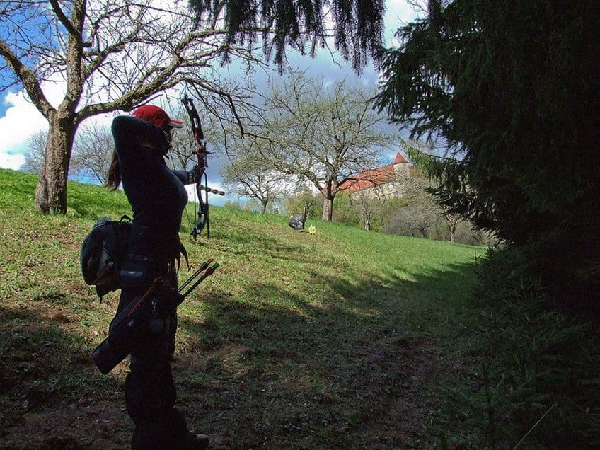 An archer in the woods aims at a plastic target of a turkey off in the distance