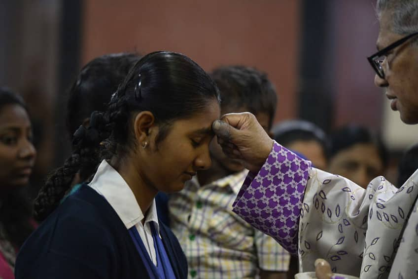 an archbishop make a sign of the cross in ash on the forehead of a young girl