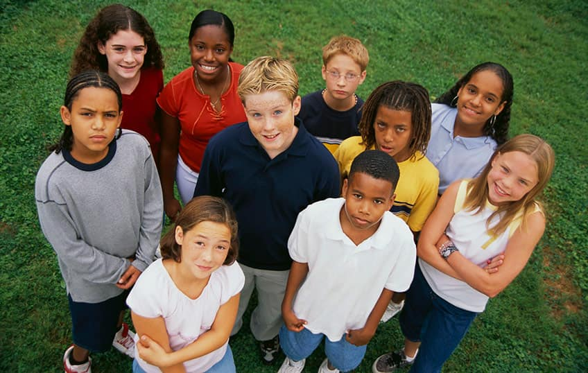 group of diverse kids including children with autism looking up at a camera