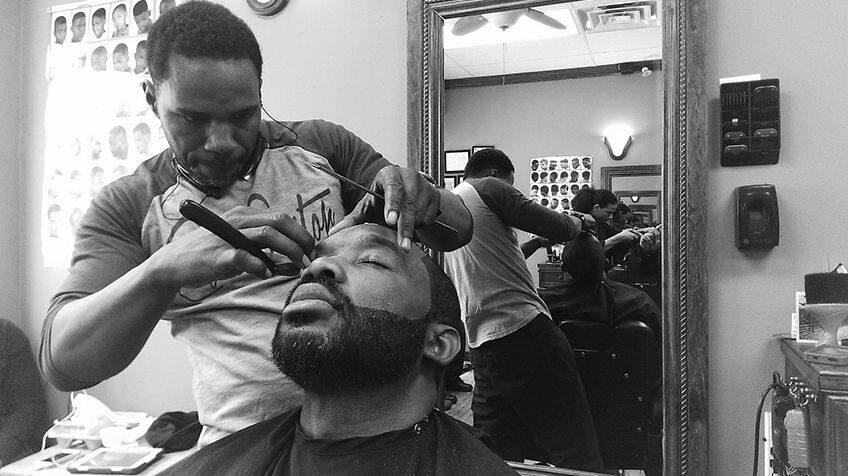 Man gets haircut in barber shop.