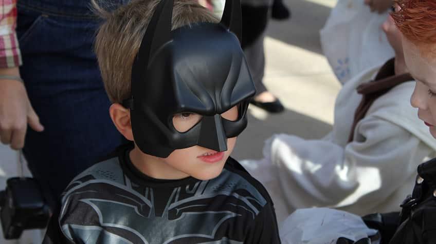 Child wears batman costume on Halloween.