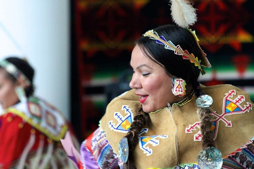 a dancer wearing buckskin regalia with beaded designs