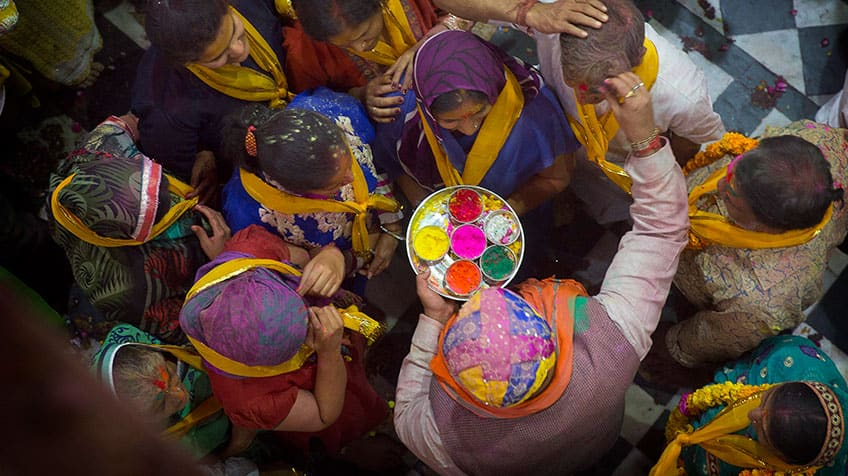 Hindu priest applies colours to devotees outside of temple for Holi festival.