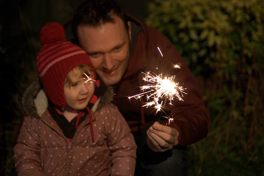 a father and child holding a sparkler
