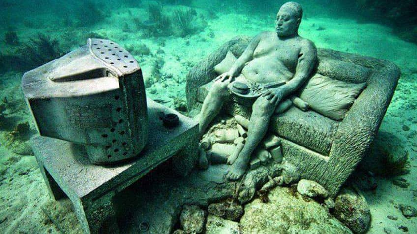 Underwater statue of a shirtless man sitting on couch in front of TV.