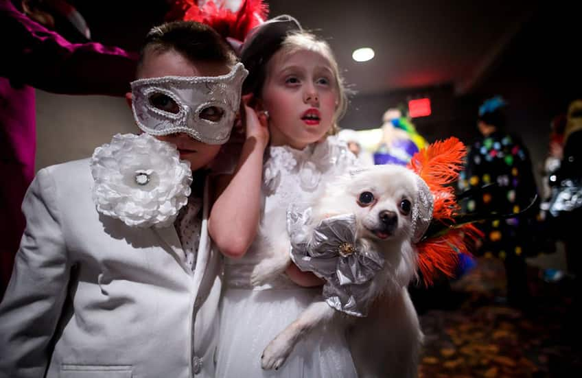 two little children dressed up in white hold their puppy also dressed in white