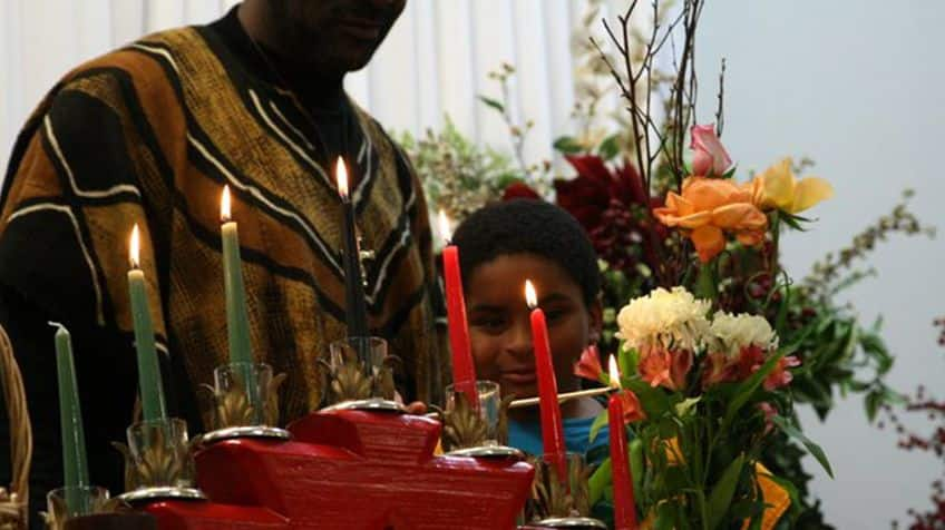 Child helps light the candles during Kwanzaa.