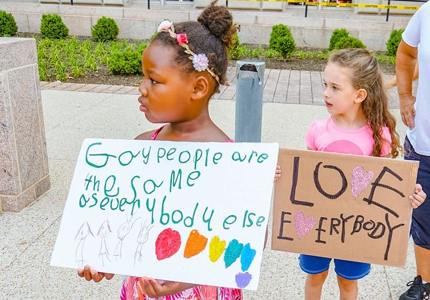 Children hold LGBTQ-positive signs.