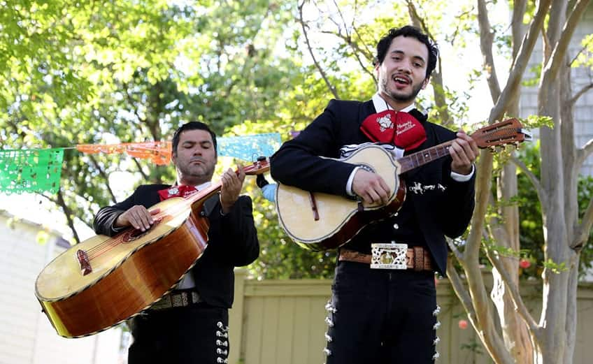two men from a mariachi band play their guitars