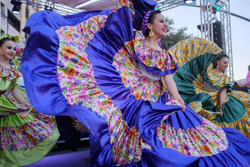 a dancer in a beautiful blue and flower striped dress twirls on the stage