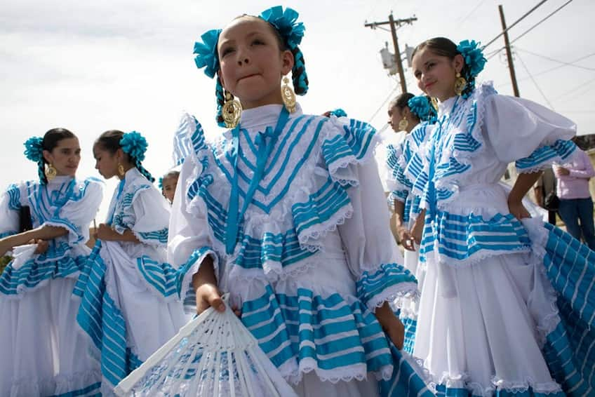 Young girls in white and blue costumes are ready to take the stage and dance