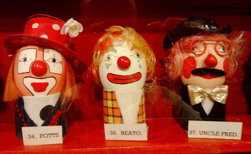 three painted ceramic clown eggs in a cabinet at the Clown Museum
