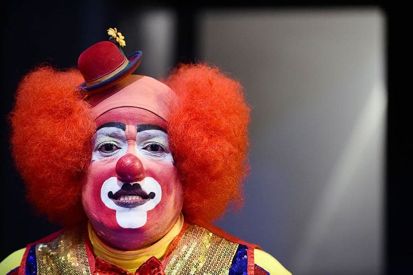 Portrait of a clown, showing his unique makeup, red hair and little hat
