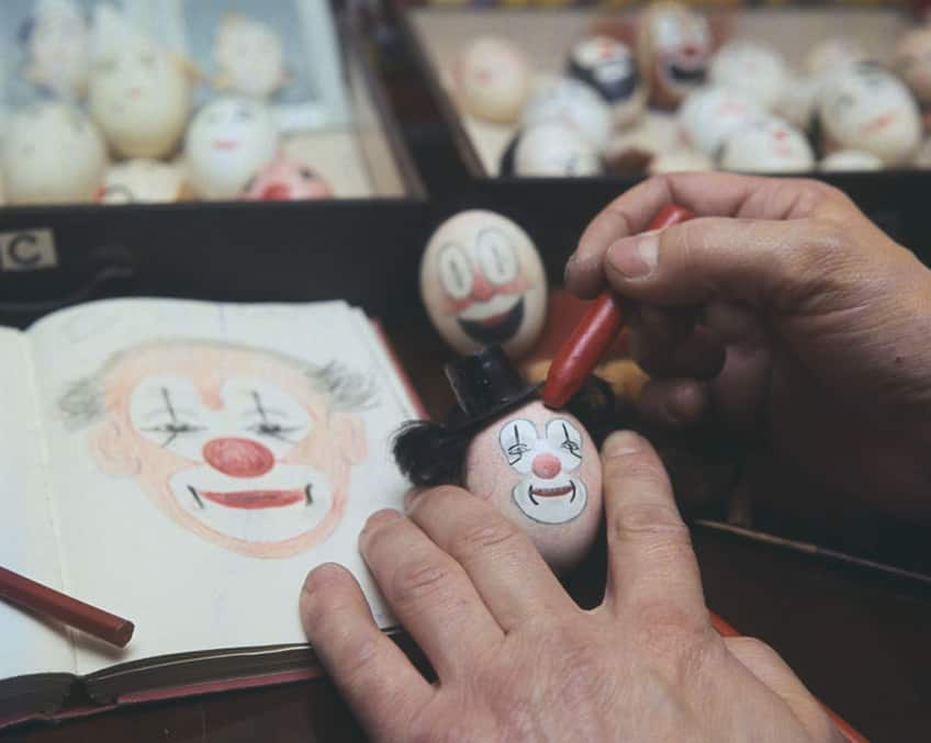 A close-up of hands decorating a new clown egg based on painting