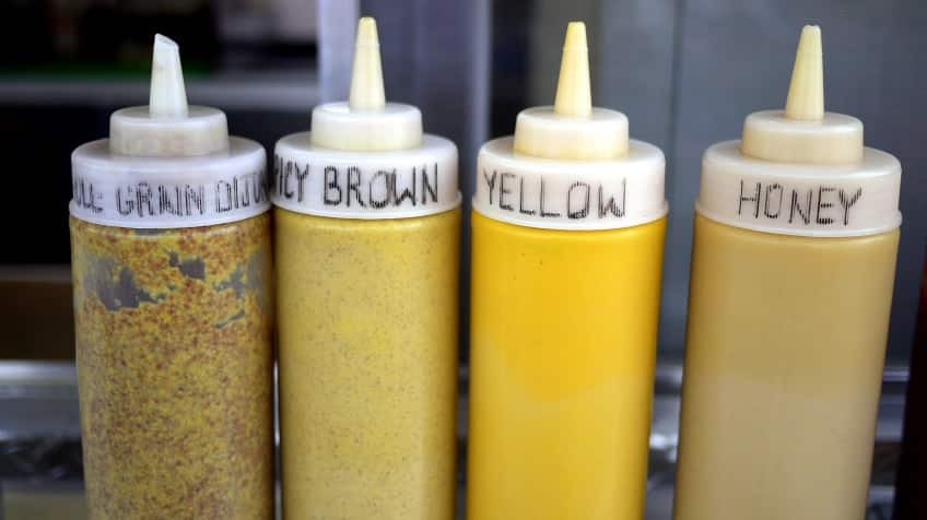 Four bottles of different kinds of mustard: yellow, honey, spicy brown and dijon