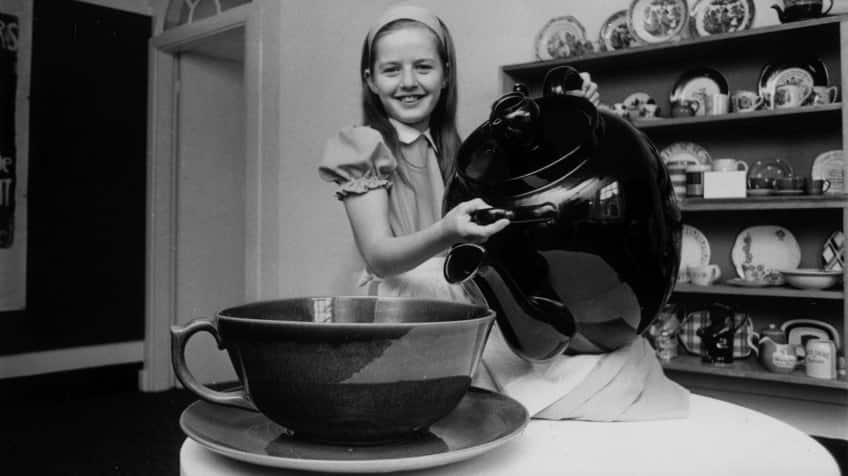A black and white photo of a little girl pouring tea from a giant teapot into a giant teacup